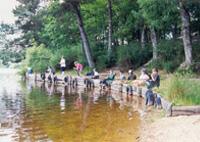 Les enfants pêchent au bord de l'étang